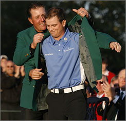 Zach Johnson receives the green jacket from last year's Masters champion Phil Mickelson.