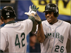Delmon Young, right, celebrates with Carl Crawford after Young's sixth-inning home run in the Devil Rays' 6-4 victory over Minnesota on Sunday. Tampa Bay is off to a fast start, trailing only Toronto in runs scored.