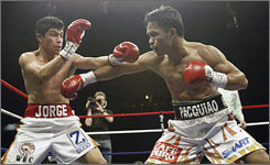 Manny Pacquiao, right, throws a punch at Jorge Solis during their title fight in San Antonio. Pacquiao retained his WBC international super featherweight crown after knocking Solis out in the eighth round.