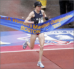 Deena Kastor crosses the finish line in fifth place in the women's division in the Boston Marathon.
