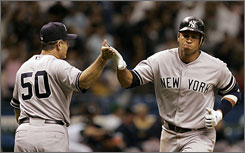 New York Yankees' Alex Rodriguez, right, gets a high five from third base coach Larry Bowa after hitting a second-inning home run in the Yankees' 10-8 loss to Tampa Bay. Rodriguez went on to hit another home run in the game, tying the record for home runs in April with 14.