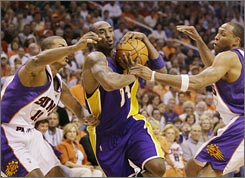 Raja Bell, left, Shawn Marion, right, and the Suns held Kobe Bryant to 15 points as Phoenix ran away with a 2-0 series lead.