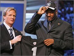 NFL commissioner Roger Goodell appears with the top pick of the draft, JaMarcus Russell, after the Oakland Raiders selected him on Saturday.