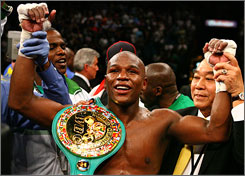 Floyd Mayweather poses with his WBC super welterweight belt after winning a decision over Oscar De La Hoya.