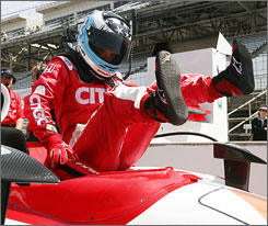 Milka Duno climbs into her car as she gets ready for rookie tests and practice at Indianapolis Motor Speedway.