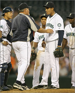 Felix Hernandez is removed from the game by Seattle manager Mike Hargrove - in the windbreaker - during the fourth inning against the Angels.