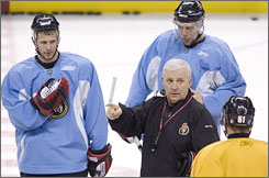 Ottawa coach Bryan Murray speaks with Oleg Saprykin, right, as Dany Heatley, back, and Jason Spezza, left, look on during a practice this season. At 64, Murray hopes to end a career-long Stanley Cup drought when the Senators line up against the Anaheim Ducks.