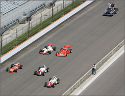 A.J Foyt and Tony George, top right, ride behind Foyt's five winning cars at the Indianapolis 500.