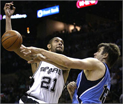 The Jazz's Mehmet Okur blocks a shot by the Spurs' Tim Duncan in Game 2. Utah needs a strong defensive effort in Game 3, especially against San Antonio's outside shooters, to get back in the series.