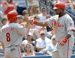 Philadelphia's Ryan Howard, right, enjoys his two-run home run with teammate Shaine Victorino during Sunday's game against the Atlanta Braves. Howard went 3-for-4 with two homers and four RBI as the Phillies swept the Braves.