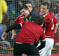 A Danish soccer fan, back to camera, tries to attack referee Herbert Fandel of Germany, center, dark shirt, during a soccer match between Denmark vs Sweden. Sweden was awarded a 3-0 win after the fan's outburst.