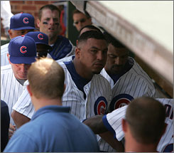 Teammates escort Carlos Zambrano out of the Cubs dugout after Friday's fight.