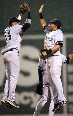 Melky Cabrera and Robinson Cano go airborne to celebrate their 6-5 rain-soaked victory over the Boston Red Sox on Sunday. The Yankees took two of three from the division-leading Sox in Fenway.