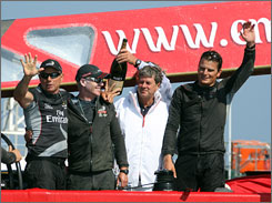 Emirates Team New Zealand's skipper Grant Dalton, left, celebrates with his crew after beating Italy's Luna Rossa and becoming the first team to go undefeated in a best-of-nine series in the 24-year history of the event.