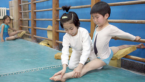 A small girl helps her classmate point her toes at the Shichahai Sports School, part of China's huge network of facilities known for recruiting young athletes in the hopes of turning them into world champions.