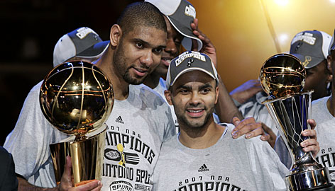The Spurs' Tim Duncan, left, and Tony Parker pose with the Larry O'Brien and MVP trophies respectively. Parker became the first European player to win the Finals MVP as he led the Spurs to a sweep of the Cavaliers and their third championship in five years. The Frenchman scored 24 points in the series-clinching game.