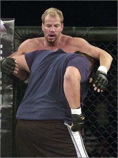 Mixed martial-arts boxer John Stover, foreground, battles former heavyweight world champion boxer Tommy Morrison during Morrison's mixed martial arts debut June 9 in Camp Verde, Ariz. Morrison scored a technical knockout in the bout's first round.