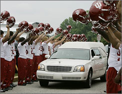 Members of the Indiana football team hoist their helmets as the hearse carrying coach Terry Hoeppner passes them following a memorial service in Bloomington, Ind.