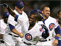 Alfonso Soriano, center, celebrates his game-winning RBI single with teammates Will Ohman, left, and Mark DeRosa, right.