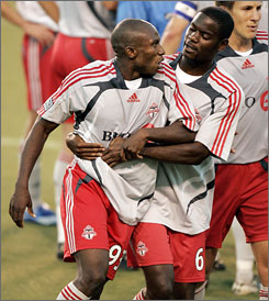 Toronto FC forward Jeff Cunningham is restrained by teammate Maurice Edu during a skirmish with Real Salt Lake. Cunningham scored a goal in Toronto's 2-1 win.