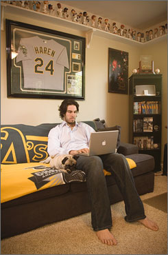 Dan Haren works on his computer while Bernie the pug relaxes. Haren's home office has plenty of baseball memorabilia, including a collection of bobblehead dolls that line the ceiling.