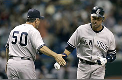 Derek Jeter gets congratulated by third base coach Larry Bowa after hitting his first home run in nearly a month.
