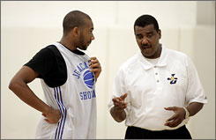 James Booker, left, takes instruction from Joy of the Game coach Carlton Evans at the Academic All-American Showcase, a basketball camp for players who excel in the classroom.