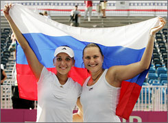 Doubles partners Elena Vesnina, left, and Nadia Petrova of Russia wave their country's colors proudly after winning their doubles match against Venus Williams and Lisa Raymond