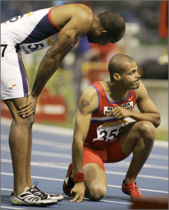 Silver medalist Bayano Kamani, left, tries to console Felix Sanchez, the Olympic 400-meter champion, after a late stumble relegated Sanchez to fourth place.