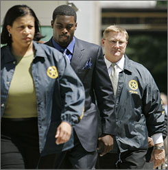 Atlanta Falcons quarterback Michael Vick, center, is escorted by U.S. Marshals, as he arrives at the federal courthouse in Richmond, Va., for his arraignment.