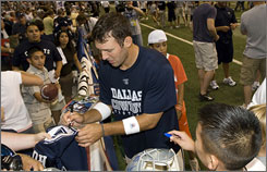 Dallas quarterback Tony Romo signs autographs for young fans at Cowboys training camp. Despite going from backup to Pro Bowler in just 10 games, Romo tries to remain level-headed and positive.