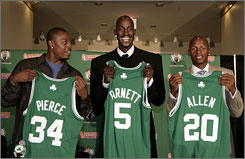 Kevin Garnett, center, sports his new Celtics jersey next to Paul Pierce and Ray Allen during a news conference welcoming the fomer Minnesota forward to Boston.