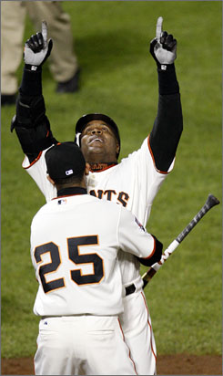 Barry Bonds points skyward after blasting his record-breaking homer.