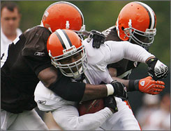 Jamal Lewis, being tackled by Willie McGinest, left, and D'Qwell Jackson on July 28, was lured to Cleveland by GM Phil Savage and a 1-year, $3.5 million contract that can reach $5 million with incentives.