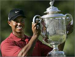 Tiger Woods hoists the Wannamaker Trophy after holding off Woody Austin to win the PGA Championship, the 13th major title of his career.
