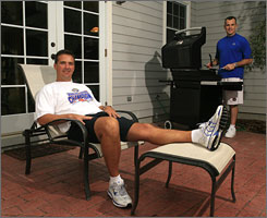 With their houses only separated by a vacant lot, friends and colleagues Urban Meyer, left, and Billy Donovan lounge in Donovan's backyard for a cookout. Meyer, the University of Florida's football coach, and Donovan, leader of the basketball team, became the first tandem of coaches in Division I-A history to win national championships in their respective sports in the same year.