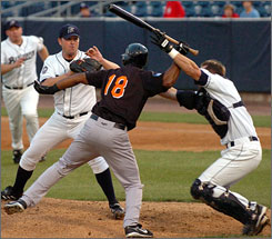 Long Island Ducks star Jose Offerman wields a bat as Bridgeport catcher John Nathans prevents the former major leaguer from bopping pitcher Matt Beech during their Atlantic League game in Bridgeport, Conn.
