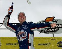 Kurt Busch celebrates in Victory Lane after he held off Martin Truex Jr. to win the rain-delayed race at Michigan International Speedway.
