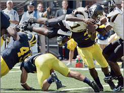 Appalachian State quarterback Armanti Edwards dives over Michigan linebacker John Thompson (49) and cornerback Brandon Harrison to score their fourth touchdown of the game during the second quarter.