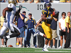 West Virginia's Steve Slaton runs away from Western Michigan's Londen Fryar on his way to the end zone.