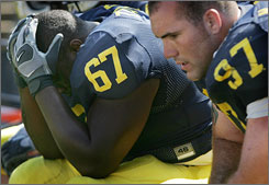 Michigan's Terrance Taylor, left, and Will Johnson look stunned during the closing seconds of the Wolverines' 34-32 loss to Appalachian State on Saturday. The loss forced Michigan out of the Top 25.