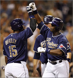 Heralded as the catalyst for San Diego's surging offense, Milton Bradley, left, congratulates Mike Cameron after Cameron blasted a grand slam in the Padres' victory on Saturday.