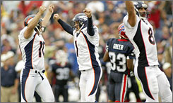 Broncos kicker Jason Elam, center, celebrates with holder Todd Sauerbrun after kicking the game-winning field goal as time expired.