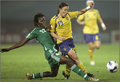 Nigeria's Christie George, left, battles Sweden's Hanna Ljungberg to clear the ball in the first half of their 2-2 tie on Tuesday.