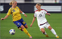 Forward Kristine Lilly  right, battling Sweden's Anna Paulson  represents the upper end of Team USA's age spectrum at 36.