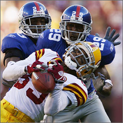 Giants defenders New York Giants Corey Webster, left, and Sam Madison try to keep a pass away from Redskins receiver Santana Moss in the second quarter.