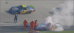 Tony Raines, left,  flings his helmet at Robby Gordon's car (27) as safety workers tend to the wreck.