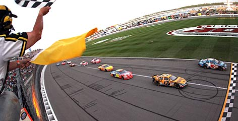 Greg Biffle's car (16) coasts along the apron of the racetrack as other cars whiz by at the end of Sunday's race. The disputed finish triggered questions from rivals and forced NASCAR to issue a statement to clarify the ruling.