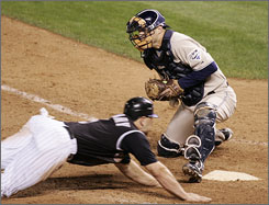The Rockies' Matt Holliday slides home past the Padres' Michael Barrett in the 13th inning on Monday night. Replays showed Holliday's hand may never have touched the plate, but home plate umpire Tim McClelland said he'd make the same call if he had to do it again.