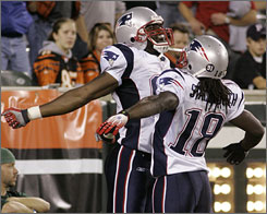 Randy Moss, left, punctuates his fourth-quarter touchdown on Monday with a jumping-chest bump with fellow receiver Donte' Stallworth.